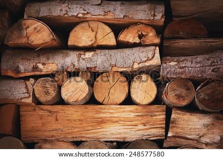 Firewood heap wood log brown winter background - stock photo