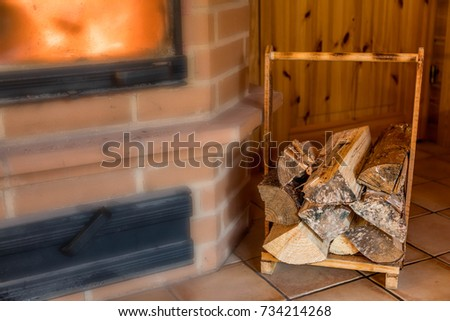 Firewood in wooden rack near the fireplace, fireplace is blurred for copy space