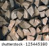 firewood stack of wood in forest - stock photo