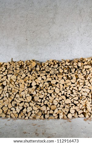 Firewood stacked in front of a rough textured light grey wall