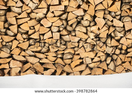 Firewood stacked in winter. Wood pile with snow stacked - stock photo