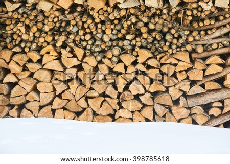 Firewood stacked in winter. Wood pile with snow stacked for firewood - stock photo