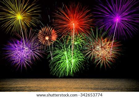 Firework celebration from the sea shore. - stock photo