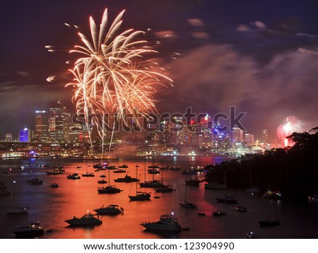 firework in Sydney new year eve event celebration bright pyrotechnic lights reflect in harbor water over city CBD - stock photo
