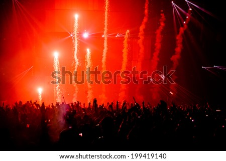 Firework pyro at music festival concert with crowd silhouette - stock photo