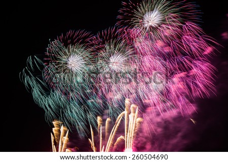 Fireworks above Honolulu Hawaii with green, blue, red, magenta, and yellow colors. - stock photo