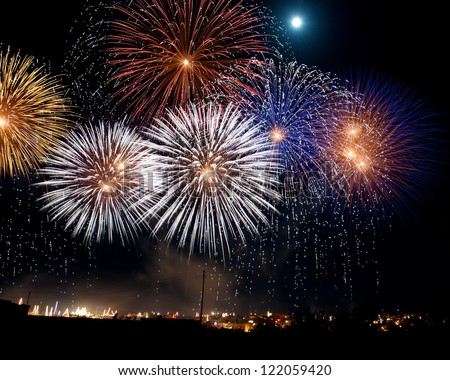 Fireworks. Colorful different amazing fireworks with the moon in Malta, dark sky background and house light in the far, Malta fireworks festival, 4 of July, Independence day, New Year, maltese - stock photo