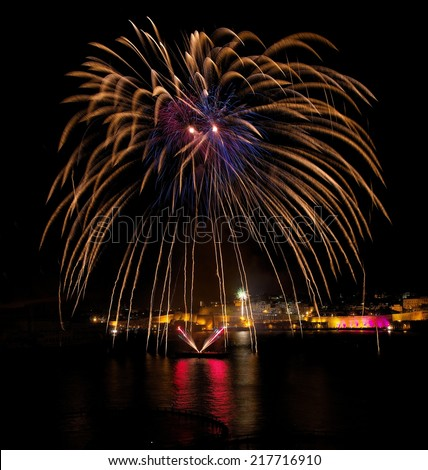 Fireworks.Colourful fireworks in Malta with dark sky and house light background,Malta fireworks festival, Independence day,New Year, fireworks explosion with reflection on sea, fireworks in Valletta - stock photo