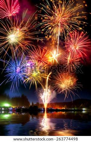 Fireworks display over lake with reflection - stock photo