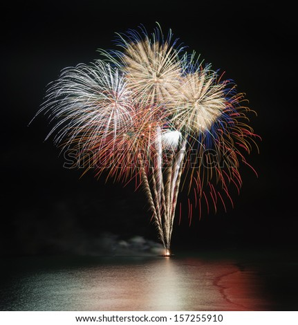 Fireworks display over sea with reflections  - stock photo