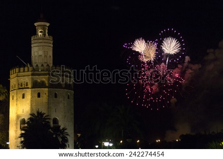 Fireworks exploding in the darkness near the Torre del Oro, Seville, Andalusia during seasonal festivities - stock photo