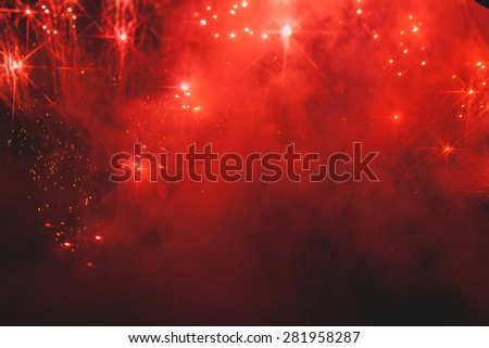 Fireworks in night sky with evergreen trees silhouetted in foreground.
