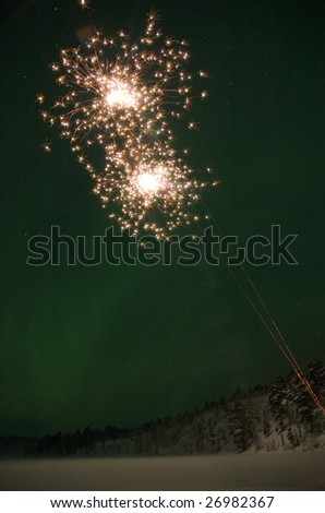Fireworks in the New Years Eve. Northern lights on the background gives the sky a green glow.