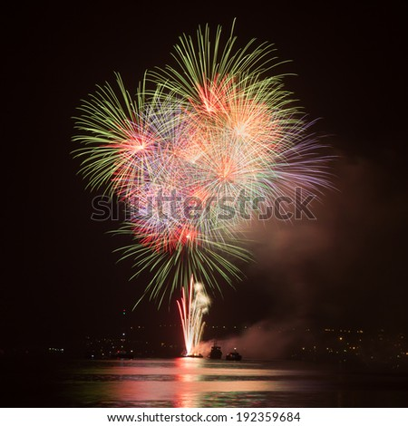 Fireworks in the night sky over water  - stock photo