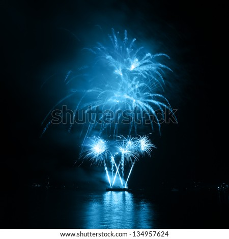 Fireworks in the night sky with reflection on water