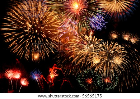 Fireworks of multiple colors bursting against a black background - stock photo