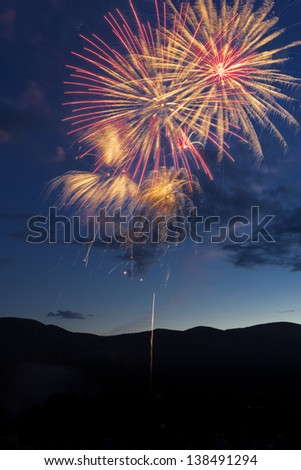 Fireworks over a mountain meadow at dusk. - stock photo