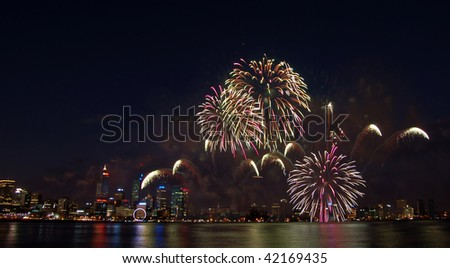 fireworks over the city with reflection in river