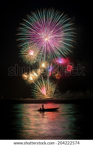 Fireworks with a fishing boat  in the sea - stock photo