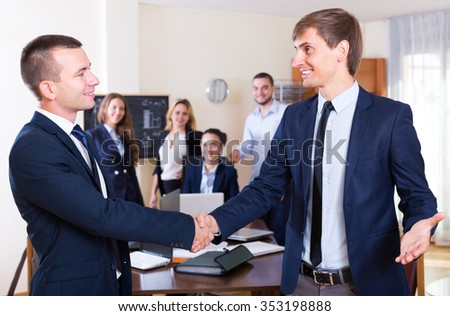 Firm handshake between two american  business partners at office meeting - stock photo