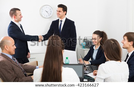 Firm handshake between two business partners on office meeting