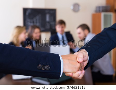 Firm handshake between two professional partners at office meeting - stock photo