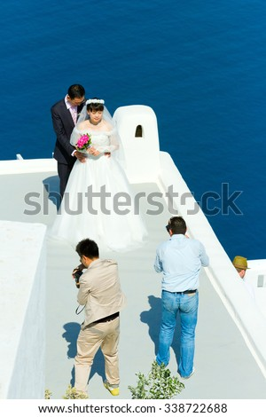 Firostefani, Greece - May 05, 2012 : Young asian just married couple on a photo session early in the morning before the tourist are on the streets.