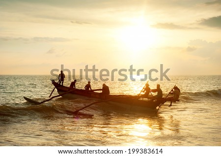 Firsherman on a boat in the ocean at sunset in Sri Lanka - stock photo