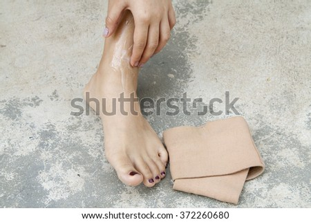 first aid accident ankle with liniment - stock photo