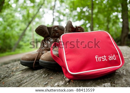 First aid kit and hiking boots in the woods - stock photo
