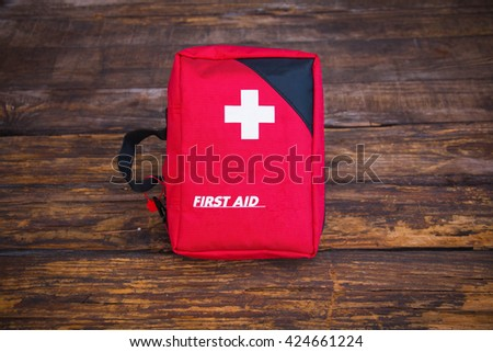 First aid medical kit on wood background. - stock photo