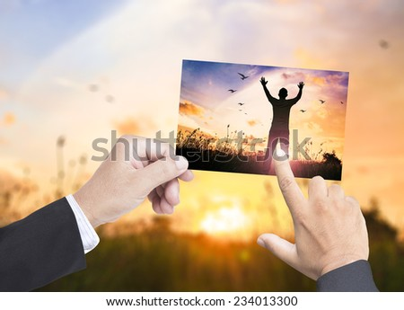 First businessman hands holds picture silhouette of man with hands raised, second businessman pointing it, compare with the actual location. - stock photo
