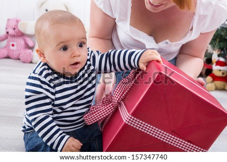 First Christmas: baby shaking big red gift box - cute little boy with his mother - stock photo
