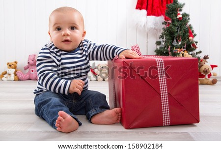 First Christmas: baby unwrapping a present - stock photo
