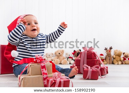 First Christmas: baby unwrapping a present - happy children eyes - stock photo