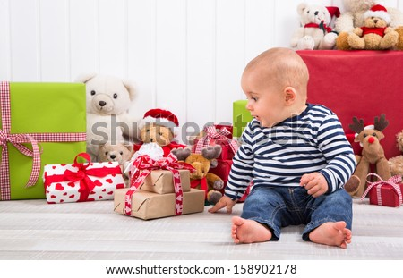 First Christmas: baby unwrapping a present - happy family - children eyes - stock photo