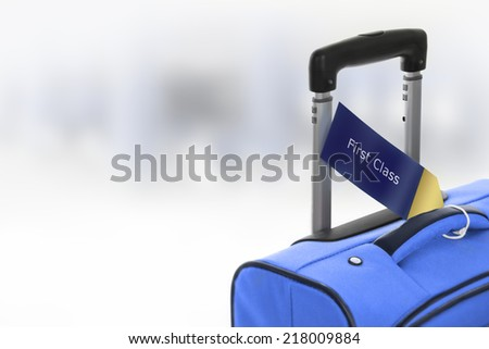 First Class. Blue suitcase with label at airport. - stock photo