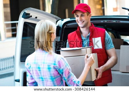 First class delivery service. Courier Delivering Package By Van. - stock photo