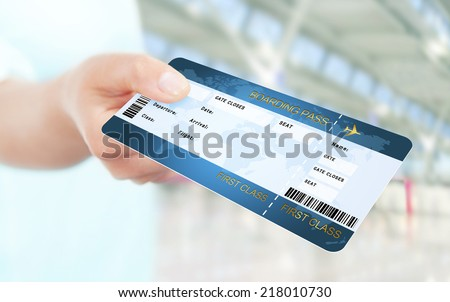 first class flight ticket holded by hand. focus on ticket - stock photo