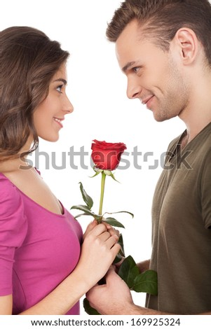 First date. Cheerful young loving couple holding a red rose and smiling while standing face to face and isolated on white background - stock photo