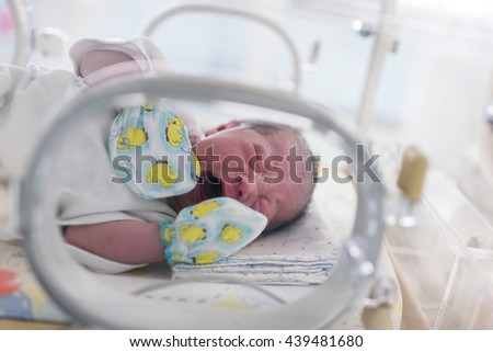 First day of Asian newborn baby in Incubator care at nursery - stock photo