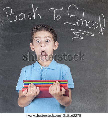 First day of school. Scared schoolboy in classroom. - stock photo
