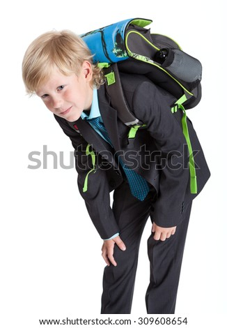 First grade pupil in uniform with heavy schoolbag, blond Caucasian boy, isolated on white background - stock photo