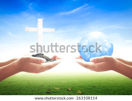 First, human hands holding the white cross. Second, human hands holding Blue planet over nature background. - stock photo