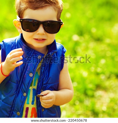 First investment concept. Portrait of stylish happy red-haired baby boy holding silver and golden coins in hand in the park. Hipster style. Sunny weather. Copy-space. Close up. Outdoor shot