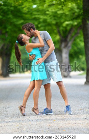 First kiss - Young couple of lovers in love passionately kissing standing on path in summer park. Full body portrait of Caucasian male and Asian female in blue sundress loving and hugging each other. - stock photo