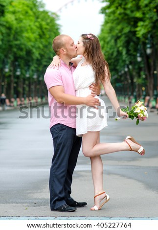 First kiss. Young couple of lovers in love passionately kissing standing on path in summer park. Full body portrait of male and female loving and hugging each other. - stock photo