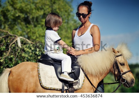 First lessons of horseback riding - stock photo