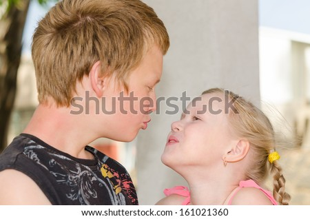 First love and kiss: two happy cute kids meeting - stock photo