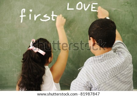 First love - boy and girl writing on board in classroom - stock photo
